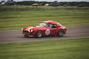 Oliver Bryant driving the red and gold 1965 AC Cobra at Goodwood Revival in 2018