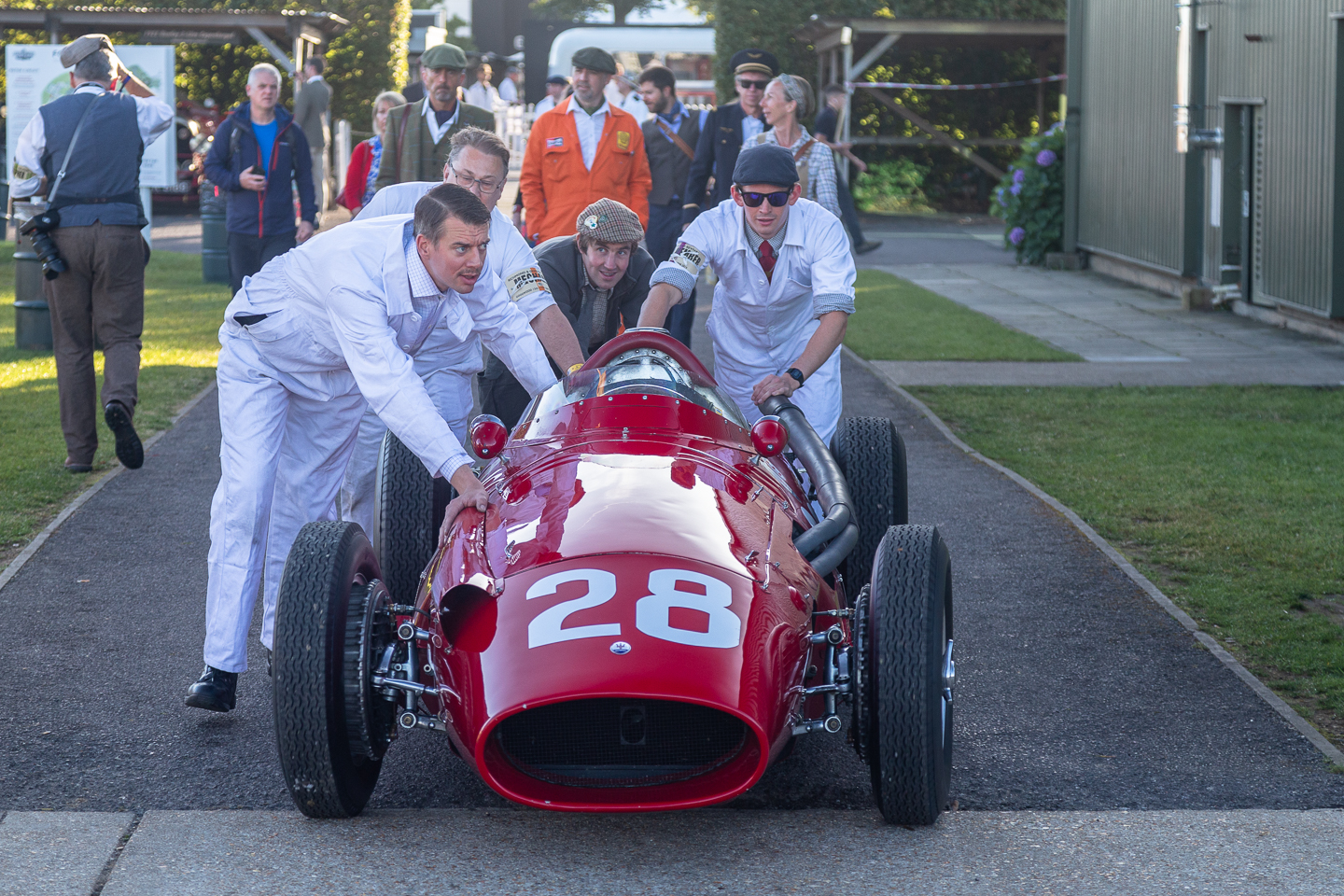Pit crew push vintage race car through the paddock at Goodwood Revival
