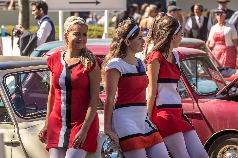 Pretty ladies in mini dresses sat on an Austin Mini