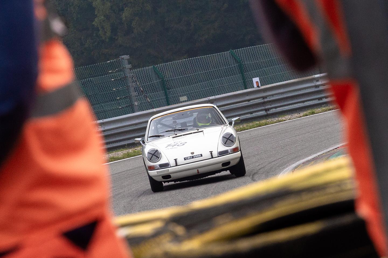 Porsche 911 photographed between race marshals