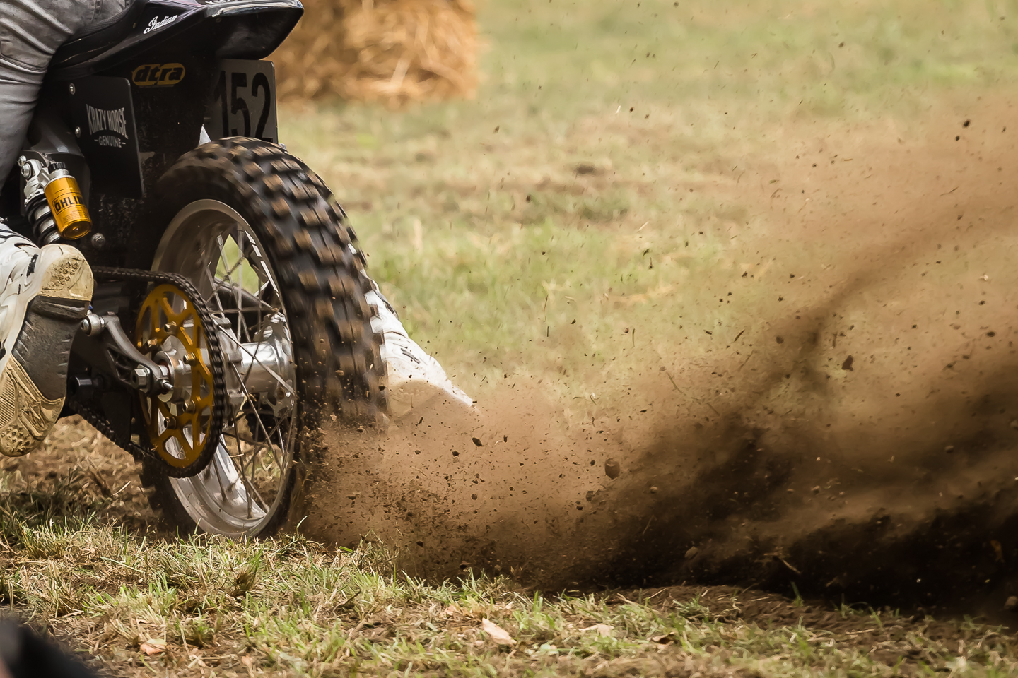 Motorcycle throwing up rooster tails of dirt