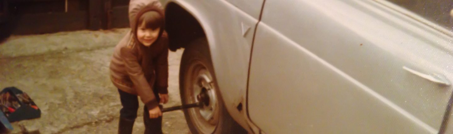 Young boy changing a wheel on a car